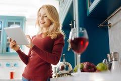 Frohe blonde Frau, die ihre Tablette verwendet Lizenzfreie Stockbilder