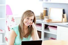 Frohe blonde Frau, die ihren Laptop und Lächeln verwendet Lizenzfreie Stockfotos