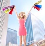 Frohe blonde Frau, die mit Papiertüten springt Stockfotografie