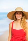 Frohe blonde Frau im roten Kleid auf dem Strand Stockbilder