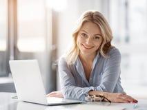 Frohe blonde Frau ist mit ihrem Arbeitstag zufrieden Stockfotografie