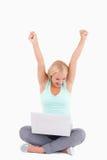 Frohe blonde Frau mit einem Laptop Stockfoto