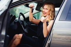 Frohe Blondine im Auto, Schlüssel halten und zeigen Daumen Stockbilder