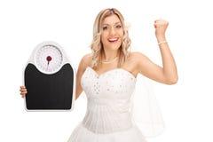 Frohe Braut, die eine Gewichtsskala hält Stockfoto