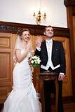Frohe Braut und Bräutigam an der ernsten Registrierung Lizenzfreie Stockfotografie