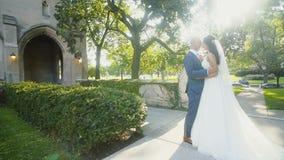 Frohe Braut und Bräutigam in der Liebe, die einander mitten in Gasse mit grünen Büschen betrachtet stock footage