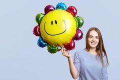 Frohe Brunettefrau trägt gestreifte Bluse, hält den Ballon, glücklich, Tochter ` s Geburtstag zu feiern, trifft die Gäste, lokali lizenzfreies stockfoto