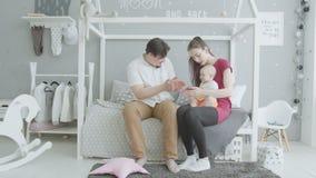 Frohe Eltern, die mit Baby im Schlafzimmer spielen stock video