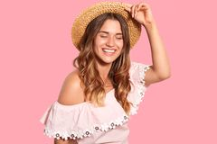 Frohe erfreute Frau mit toothy Lächeln, trägt Kopfbedeckung, moderne Bluse, kichert positiv, genießt angenehme Momente im Leben, lizenzfreie stockbilder