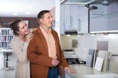 Frohe erwachsene Familie, die Küchenmöbel vorwählt stockfotos