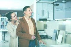 Frohe erwachsene Familie, die Küchenmöbel vorwählt lizenzfreies stockbild