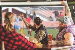 Frohe erwachsene Männer, die Bier in der Bar trinken Stockfoto