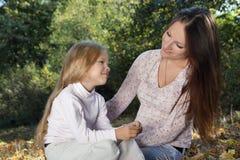 Frohe Familie, die auf dem Herbstlaub sitzt Stockbild