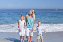 Frohe Familie, die auf den Strand geht stockfotos