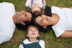 Frohe Familie, die in einem Kreis auf dem Gras liegt lizenzfreie stockfotografie