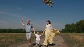 Frohe Familie, die einen Drachen und einen Betrieb auf der Straße mit ihr fliegt stock footage