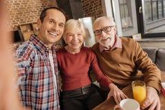 Frohe Familie, die selfies in der Küche nimmt stockbilder