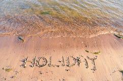 Frohe Feiertage geschrieben in den sandigen Strand Lizenzfreie Stockfotos