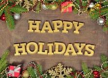 Frohe Feiertage goldener Text und Fichtenzweig und Weihnachtsdekor Stockfotografie