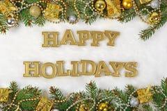 Frohe Feiertage goldener Text und Fichtenzweig und Weihnachtsdekor Lizenzfreies Stockfoto
