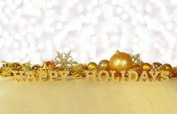 Frohe Feiertage goldener Text und goldene Weihnachtsdekorationen Lizenzfreie Stockfotos