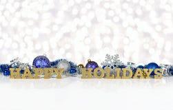 Frohe Feiertage goldener Text und Weihnachtsdekorationen Lizenzfreies Stockbild