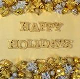 Frohe Feiertage goldener Text und Weihnachtsdekorationen Stockfotografie