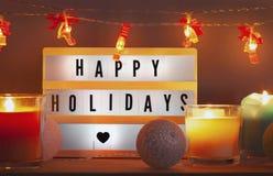 Frohe Feiertage lightbox und Weihnachtsdekorationen mit Kerzen lizenzfreies stockbild
