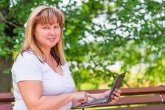 Frohe Frau auf einer Parkbank mit einem Laptop Stockfotos