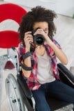Frohe Frau auf Rollstuhl unter Verwendung der Kamera Lizenzfreies Stockfoto