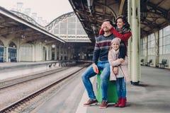 Frohe Frau bedeckt Augen ihres Ehemanns, macht Überraschung Freundliche Familie des Mutter-, Vater- und Tochterstands zusammen an lizenzfreies stockbild