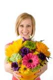 Frohe Frau bietet Blumenstrauß an Stockfotografie