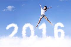 Frohe Frau, die auf die Wolke mit Nr. 2016 springt Lizenzfreie Stockfotografie