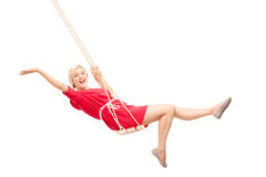 Frohe Frau, die auf einem Schwingen schwingt Lizenzfreies Stockfoto