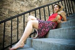 Frohe Frau, die auf Treppen sich entspannt Lizenzfreie Stockbilder