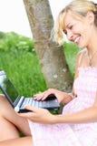 Frohe Frau, die draußen einen Laptop verwendet Stockbild
