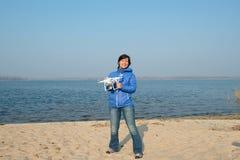 Frohe Frau, die ein quadcopter, Brummen hält und das Leben auf Th genießt Lizenzfreie Stockfotografie