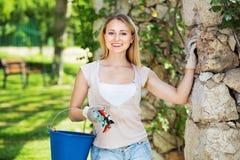Frohe Frau, die Gartenbauinstrumente im Garten hat lizenzfreies stockfoto