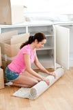 Frohe Frau, die heraus einen Teppich rollt Stockfotografie
