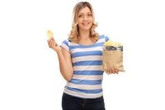 Frohe Frau, die Kartoffelchips isst Lizenzfreies Stockbild