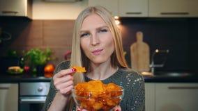 Frohe Frau, die Kartoffelchips isst Schöne junge Frau, die Kartoffelchips genießt und Kamera beim herein sitzen betrachtet stock video
