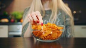 Frohe Frau, die Kartoffelchips isst Schöne junge Frau, die Kartoffelchips genießt und Kamera beim herein sitzen betrachtet stock video footage