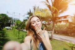 Frohe Frau, die selfie mit dem Luftkuß hält die Linsenkamera, reisend nach sonniges Thailand mit Palmen und grünem Gras nimmt Stockfotografie