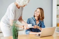 Frohe Frau, die am Tisch sitzt Lizenzfreie Stockfotos