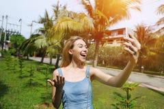 Frohe Frau, die Videoanruf mit dem intelligenten Telefon, reisend nach sonniges Thailand mit Palmen und grünem Gras macht Stockfotos
