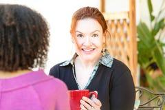 Frohe Frau gesetzt mit Freund am Café Lizenzfreies Stockfoto