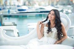 Frohe Frau im eleganten Kleid am sonnigen Tag am Jachthafen Lizenzfreies Stockfoto