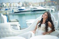 Frohe Frau im eleganten Kleid am sonnigen Tag am Jachthafen Lizenzfreie Stockbilder