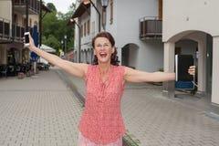 Frohe Frau mit den offenen Armen auf Stadt-Straße Lizenzfreie Stockfotos