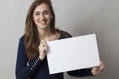 Frohe Frau 20s, die eine Anzeige machend genießt, wenn ein leerer Einsatz angezeigt wird Lizenzfreie Stockfotos